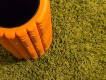 Pomarańcze piankowy rolownik na zielonym tle Fotografia Stock