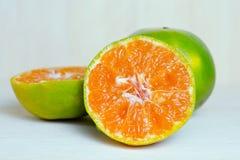 Pomarańczowa owoc z przyrodnim widokiem na drewnianym tle Obrazy Stock