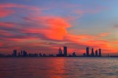 Pomarańczowej czerwieni niebo podczas zmierzchu i Bahrajn linii horyzontu Obrazy Stock