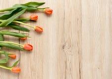 Pomarańczowi tulipany na Brown Drewnianym tle Fotografia Stock