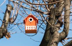 Pomarańczowy drewniany ptaka dom w drzewie w parku Zdjęcie Royalty Free