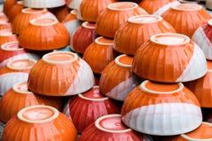 Pomarańczowy puchar ceramiczny przy magazynem Zdjęcie Royalty Free