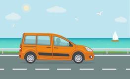 Pomarańczowy samochód na drodze blisko morza Fotografia Stock