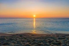 Pomarańczowej czerwieni zmierzchu wschód słońca na plażowym piaska brzeg i morze oceanu horyzoncie Obrazy Stock