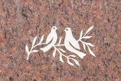 Pombas e ramo de oliveira na superfície da pedra Fotografia de Stock Royalty Free