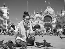 Pombos de alimentação da jovem mulher bonita na praça San Marco Black e no branco Imagens de Stock Royalty Free