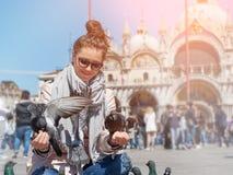 Pombos de alimentação da jovem mulher no quadrado de San Marco Fotos de Stock