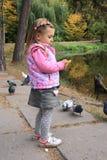 Pombos de alimentação da menina Fotos de Stock Royalty Free
