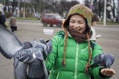 Pombos de alimentação da menina na rua, Kostroma, Russ Imagem de Stock Royalty Free
