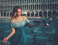 Pombos de alimentação da mulher bem vestido bonita no quadrado de San Marco Imagens de Stock