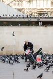 Pombos de alimentação do ancião perto do centro de Pompidou, Paris, França Imagem de Stock