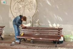 Pombos de alimentação do homem novo, a rua de Arbat Fotografia de Stock