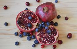Pomegaranate wooden board. Pomegranate fruit on the wooden board, with berries royalty free stock photos