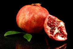 Pomegranate. Fresh ripe pomegranate with a half on a reflexive black Stock Images