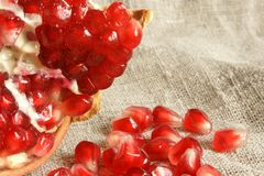 Pomegranate. Open pomegranate with seeds on a cloth background stock images