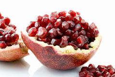 Pomegranate. Half of a pomegranate with lots of seeds accompanied by additional loose seeds and fruit parts Stock Photography