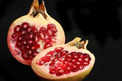 Pomegranate. Sliced pomegrnate fruit over a black background Stock Photo