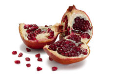 Pomegranate. Parts of pomegranate and seeds around isolated on white Royalty Free Stock Image
