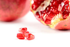 Pomegranate. Grains closeup with the cut and whole fruits on the backstage Stock Photography