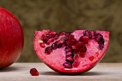 Pomegranate. Wedge of pomegranate on cutting board showing the lusciousness of the pulp Stock Photography
