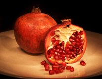 Pomegranate. Sliced on plate with dark background Stock Photos