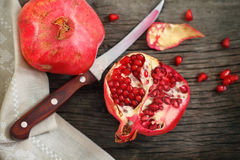 Pomegranate. Juicy riped pomegranate and knife on the wooden table royalty free stock photo