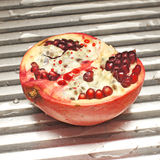 Pomegranate. The pulled down pomegranate on a metal board royalty free stock images
