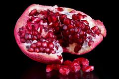 Pomegranate. A piece of open pomegranate with seeds isolated on black background Stock Photography
