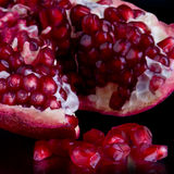 Pomegranate. A piece of open pomegranate with seeds isolated on black background Royalty Free Stock Image
