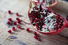 Pomegranate with arils on wooden board royalty free stock image