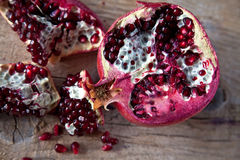 Pomegranate with arils on wooden board Royalty Free Stock Photography