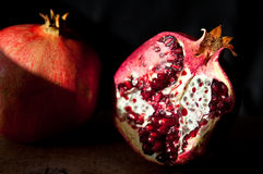 Pomegranate with arils on wooden board royalty free stock images