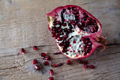 Pomegranate with arils on wooden board. Pomegranate with arils on brown wooden board stock images