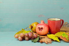 Pomegranate, autumn leaves and tea cup over wooden background Stock Images