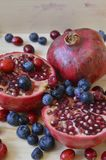 Pomegranate with berries. Pomegranates and berries served on the table Stock Image