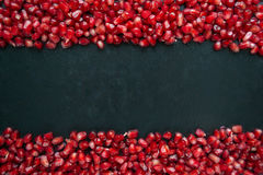 Pomegranate on a black background. Scattered ripe pomegranate grains. macro Stock Photos