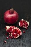 Pomegranate on black wood Stock Photo
