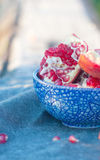 Pomegranate in the blue plate on the material Stock Photography