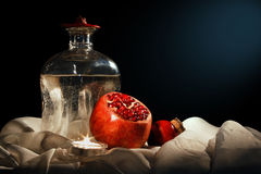 Pomegranate and a bottle of water on the fabric background Royalty Free Stock Photography