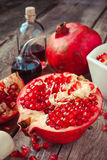Pomegranate and bottles of essence or tincture on table Stock Images