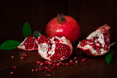 Pomegranate with broken segments and leaves Stock Images