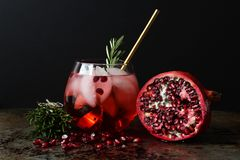 Pomegranate cocktail. Pomegranate fruit with cross section and elegant cocktail front view. Copy space royalty free stock photography