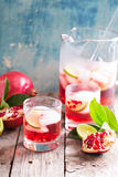 Pomegranate cocktail with lime slices Stock Images