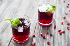 Pomegranate cocktail with pomegranate seeds, lime and mint. alcoholic and non-alcoholic Royalty Free Stock Images