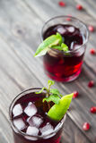 Pomegranate cocktail with pomegranate seeds, lime and mint. alcoholic and non-alcoholic Royalty Free Stock Photo