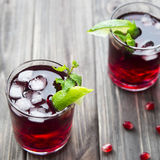 Pomegranate cocktail with pomegranate seeds, lime and mint. alcoholic and non-alcoholic Stock Photos