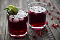 Pomegranate cocktail with pomegranate seeds, lime and mint. alcoholic and non-alcoholic Stock Images