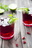 Pomegranate cocktail with pomegranate seeds, lime and mint. alcoholic and non-alcoholic Stock Photography