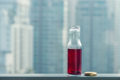 Pomegranate cold juice in bottles opposite the metropolis. And skyscrapers Royalty Free Stock Photos