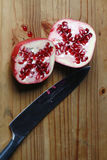 Pomegranate cut in half with sharp knife Royalty Free Stock Photography